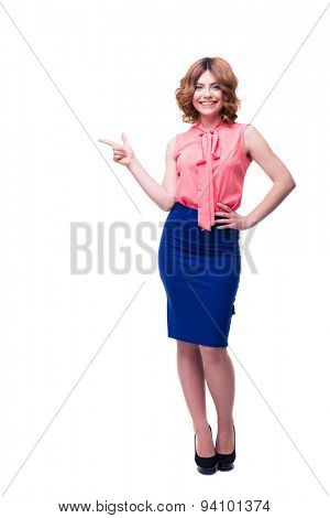 Full length portrait of a smiling woman pointing finger away and looking at camera isolated on a white background