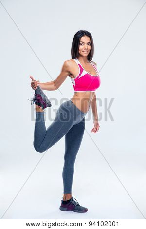 Full length portrait of a happy sporty woman stretching leg over gray background. Looking at camera