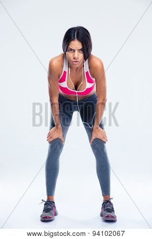 Full length portrait of a tired fitness woman resting over gray background and looking at camera