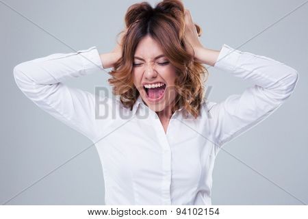 Young businesswoman shouting over gray background