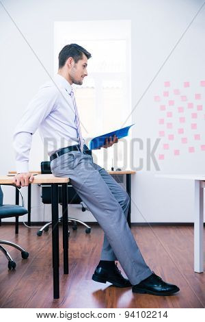 Side view portrait of a pensive businessman leaning on the table with folder
