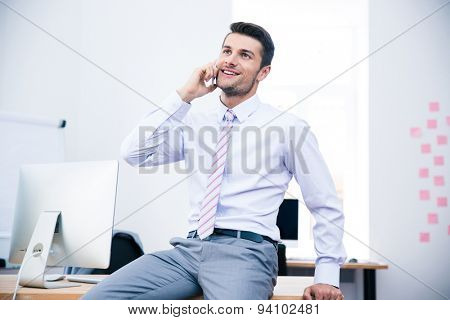 Happy businessman sitting on the table and talking on the phone in office