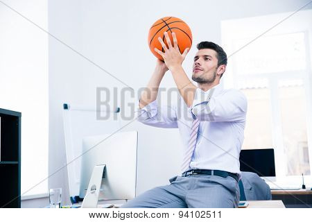 Formal businessman sitting on the table with ball in office