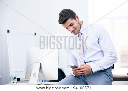 Happy businessman sitting on the table and using smartphone in office