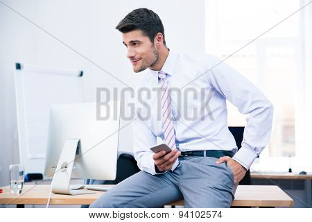 Happy businessman sitting on the table and using smartphone in office. Looking away