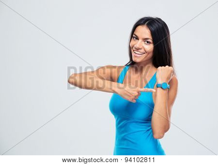 Happy fitness woman pointing on fitness tracker over gray background