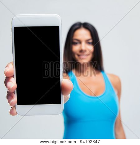 Happy woman showing blank smartphone screen over gray background. Focus on smartphone