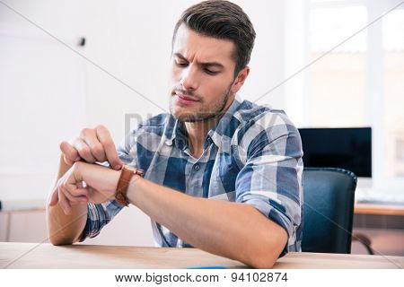 Handsome young businessman in casual cloth looking on wrist watch