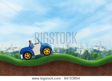 Happy businessman driving a toy car