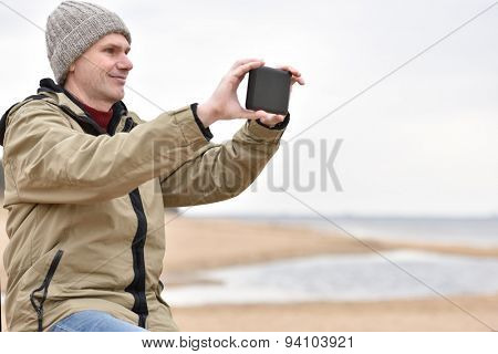 Mature man in jacket and knit hat makes photo using his tablet on the beach