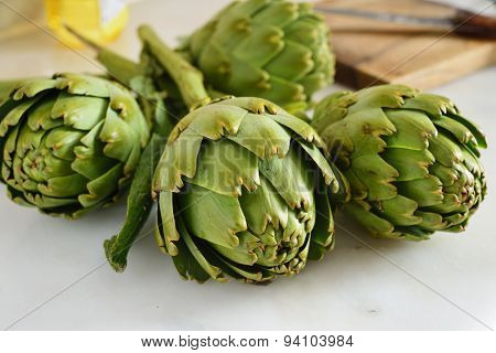 Four raw artichokes on a marble table