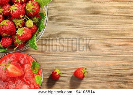 Glass of strawberry smoothie with berries on table close up