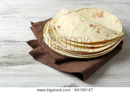 Stack of homemade whole wheat flour tortilla on napkin, on wooden background