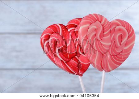 Bright lollipops in shape of heart on wooden background