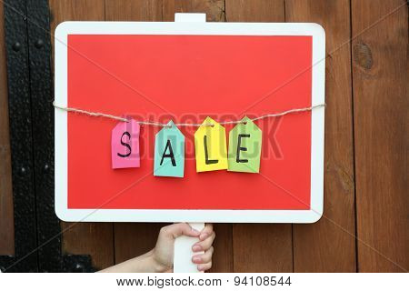 Sale sign on wooden fence background
