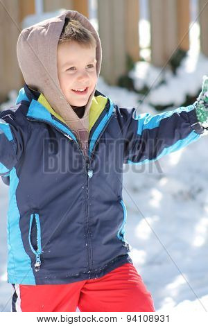 Happy boy playing in the snow