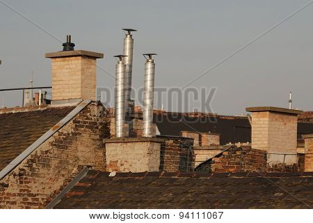 Chimneys on roofs in late afternoon light