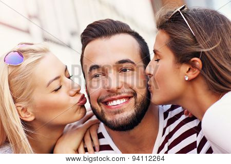 A picture of two attractive women kissing a man in the city