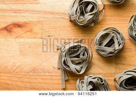 black tagliatelle pasta on wooden table