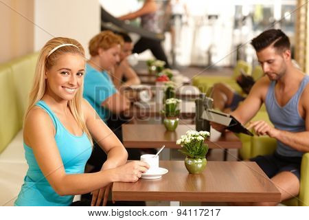 Pretty young blonde girl having coffee-break in gym.