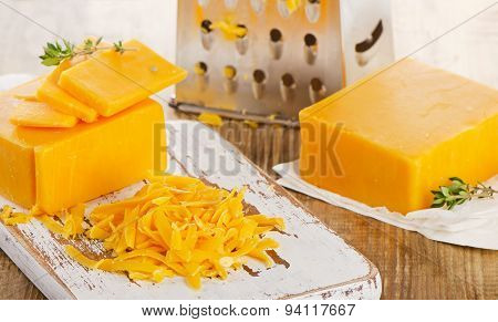 Grated Cheddar Cheese On  A Wooden Cutting Board.