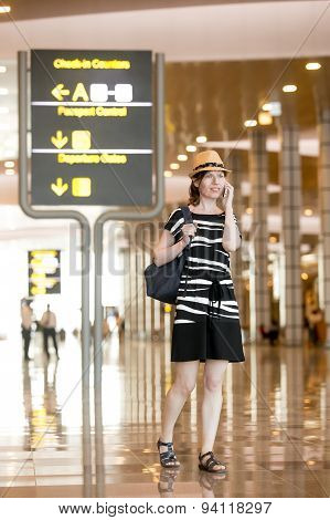 Woman Speaking On Smartphone In Airport