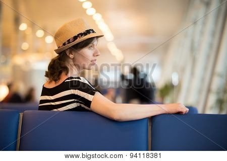 Young Female Traveler Sitting In Waiting Lounge