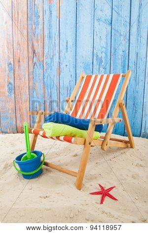 Chair and toys at the beach in front of blue background