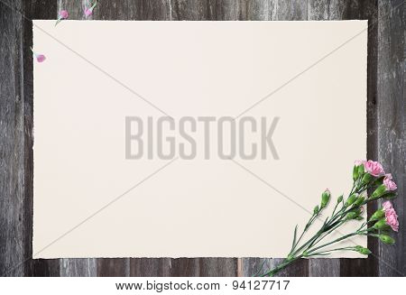 Empty White Paper And Pink Carnation On Old Wooden Table.
