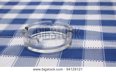 Vintage glass ashtray on blue plaid tablecloth