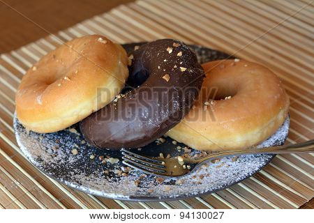 Delicious donuts with icing sugar on a plate on a wooden table