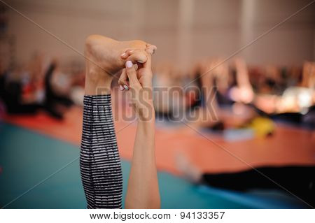 Woman Is Doing Yoga . Hand Holds Feet