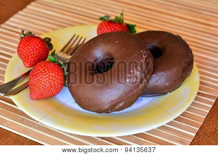 Homemade donuts with brown chocolate and fresh strawberries