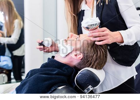 Woman barber shaving customer in her shop, applying soap with a brush