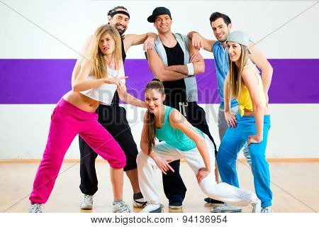 Young men and women dancing zumba modern group choreography in dance school