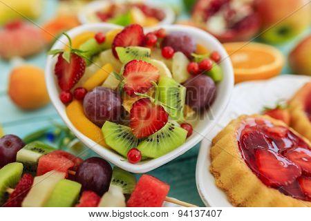 Healthy fruit salad, fruit skewer, strawberry tart - summer party