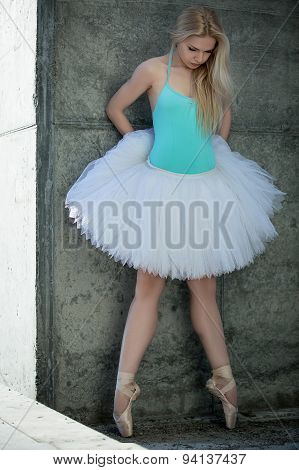 Graceful dancer with blond hair on the background of gray concre