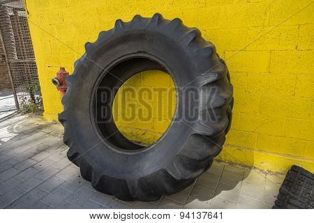Big tire leaning against yellow wall