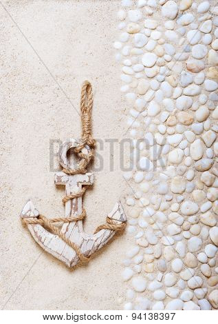 Decorative anchor on the sea sand. Marine background