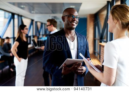 Black Executive And White Executive Smiling At Eachother