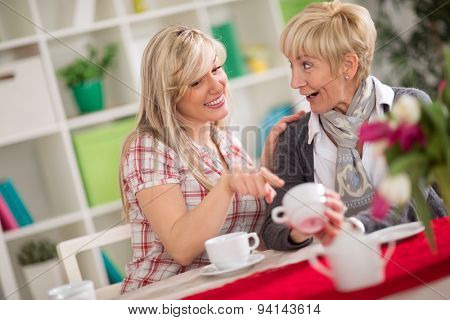 two females talking and drinking coffee, younger woman augury looking at cup of coffee