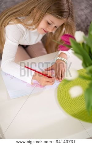 Adorable girl making gift card for mother day, writing in living room