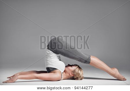Full length of a young woman stretching body. Gray Background.