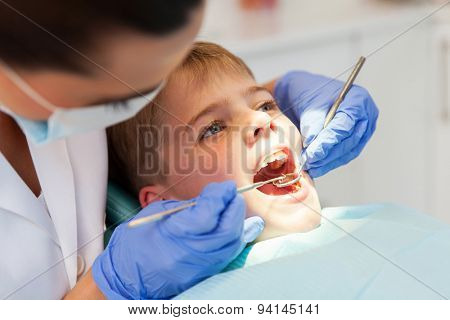 dentist examining boys teeth close up