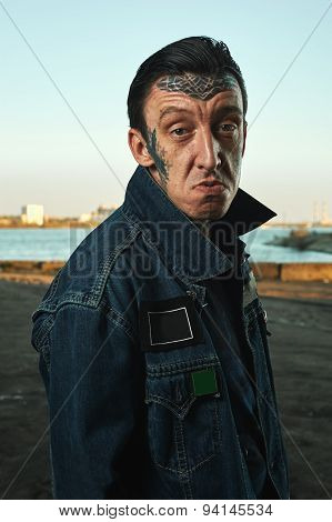 Hooligan With Tattooed Face In Denim Jacket Making Faces