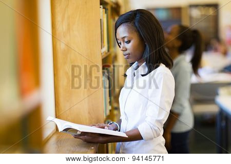 beautiful afro american college girl reading a book in library