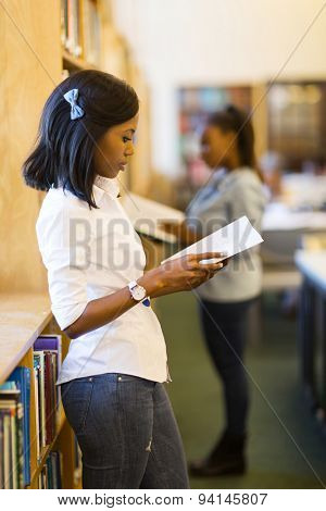 young african woman reading a book in library