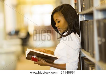 beautiful female african american student reading a book in library