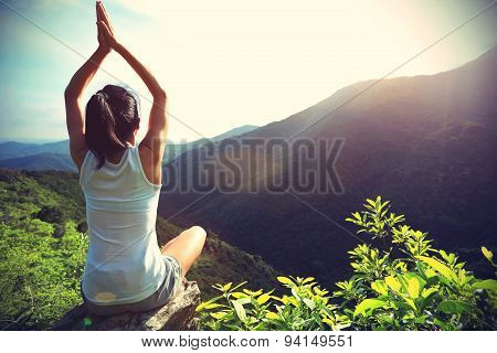 young yoga woman sit meditation on mountain peak rock