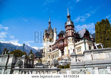 Spring view of Peles Castle with snowy Bucegi Mountains in the background.